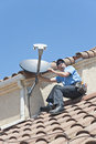 Satellite installer on roof installation of dish tv system in sitting position Stock Photos
