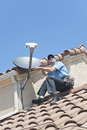 Satellite installer on roof installation of dish tv system spanish tiled Royalty Free Stock Photos