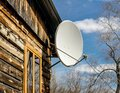 Satellite white dish on the wall under the roof of a wooden house against a blue spring sky and tree branches without leaves, Royalty Free Stock Photo
