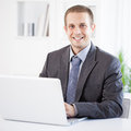 Satisfied businessman a sitting at his office and smiling Royalty Free Stock Photos