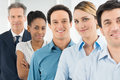 Satisfied businesspeople standing in a row group of happy multi multiethnic looking at camera Stock Photo