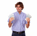 Satisfied charming man smiling holding dollars portrait of a in blue shirt and cash on isolated background Royalty Free Stock Photo