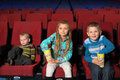 Satisfied children watching a movie and eating popcorn in the cinema Royalty Free Stock Images