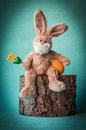 Satisfied Easter rabbit with tulip and egg on the stump. Royalty Free Stock Photo