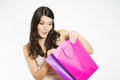 Satisfied female customer with her purchase beautiful young held in a purple recyclable paper shopping bag smiling happily at the Royalty Free Stock Photo