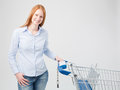 Satisfied female customer with shopping cart a holding a and looking at the camera Stock Image