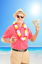 Satisfied gentleman holding a cigar and us dollars on beach Royalty Free Stock Images