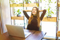 Satisfied with a job done. Happy young businesswoman holding hands behind head and smiling while sitting at her working Royalty Free Stock Photo