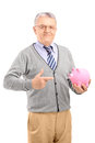 Satisfied mature gentleman holding a piggy bank and gesturing Stock Photography