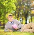 Satisfied mature gentleman in a park holding a piggy bank shot with tilt and shift lens Stock Photos