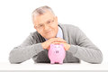 Satisfied mature gentleman posing over a piggy bank isolated on white background Stock Photos