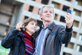 Satisfied senior couple with house keys making selfie together makes Stock Images