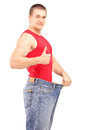 Satisfied weight loss man in a pair of old jeans giving a thumb Royalty Free Stock Photography