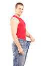 Satisfied weight less man in an old pair of jeans looking at cam camera isolated on white background Royalty Free Stock Images