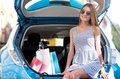 Satisfied woman sitting on trunk of car so good day young with sunglasses the open her hybrid after shopping Royalty Free Stock Photography
