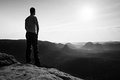 Satisfy tall hiker in grey shirt and dark trousers. Sprtsman on the peak of sharp rock edge watching down to landscape. Royalty Free Stock Photo
