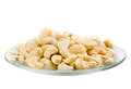 Saucer with a row cashew nuts isolated on white background images collected from four shots to increase the zone of sharpness Stock Image