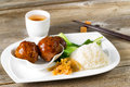 Saucy meatballs meal in white plate ready to eat close up front view asian rice and bok choy on chopsticks and green tea Stock Images