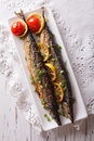 Saury grilled with vegetables on a plate close-up. vertical top Royalty Free Stock Photo