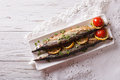 Saury grilled with vegetables on a plate. Horizontal top view Royalty Free Stock Photo