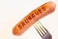 Sausage with an inscription pinned on a fork, on a white background.