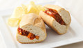Sausage and peppers sandwich served with a side of potato chips Royalty Free Stock Photo