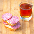 Sausage sandwich and hot sweet beverage tea Stock Images