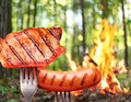 Sausage and steak on a fork in the background bonfire in the forest Stock Photography