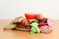 Sausage on the table of assorted cold cuts and bread cucumber and tomato Stock Photos