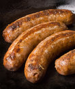 Sausages in a black frying pan Stock Images