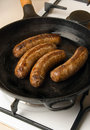 Sausages in a black frying pan with gas stove Stock Photo