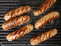 Sausages cooking on griddle viewed from above being cooked plate Royalty Free Stock Photo