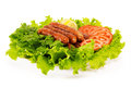 Sausages delicious laid on lettuce leaves with tomato slices and parsley Royalty Free Stock Image