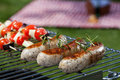 Sausages on grill white grilling during a summer barbecue Stock Images