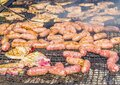 Sausages and pork steaks on the large barbeque Royalty Free Stock Photo