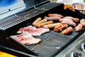 Sausages and steaks cooking on a barbecue grill delicious tasty Royalty Free Stock Photos