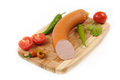Sausages with a tomato and pepper on cutting board Royalty Free Stock Photo