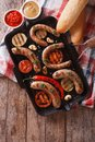 Sausages with vegetables in a pan grill.  Vertical top view Royalty Free Stock Photo
