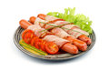 Sausages wrapped in bacon three pork garnished with lettuce grilled tomatoes spring onion and mustard on plate isolated on white Royalty Free Stock Photos