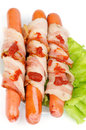 Sausages wrapped in bacon three pork garnished with lettuce and ketchup isolated on white background Stock Images
