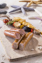 Saussages with scallop skewers on cutting board on the beach
