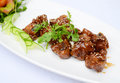 Sauteed pork ribs with seasame and herbs on white dish Royalty Free Stock Photo