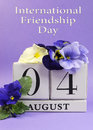 Save the date white block calendar for august international friendship day vertical decorated with blue and pansy violas on blue Stock Image