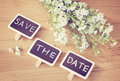 Save the date written on blackboard with flower retro filter effect Stock Photography