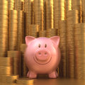 Saving gold coin piggy bank with stacks of coins in the background Royalty Free Stock Photo