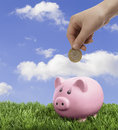 Saving hand depositing coin into piggy bank Royalty Free Stock Photo
