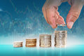 Saving money concept. hand putting coin to stacks of coins. Royalty Free Stock Photo