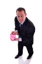Saving money image of a businessman in a piggy bank image is isolated on white Royalty Free Stock Photography