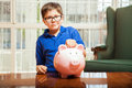 Saving money on a piggy bank clever kid with glasses dropping coin his at home Stock Photo