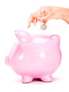 Saving money in a piggybank isolated over white background Stock Photography